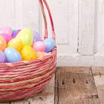 18170425-plastic-easter-eggs-in-easter-basket-on-rustic-wooden-background